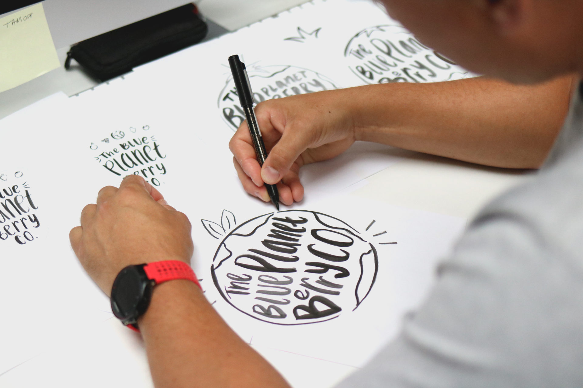 person drawing blue planet berry co logo on paper